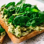 Avocado on toast, with basil leaves